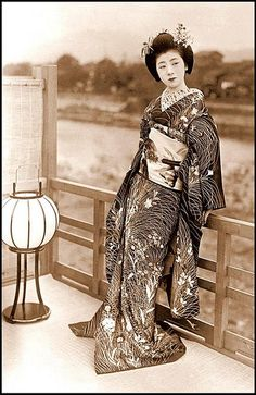 THE GRACEFUL CURVES AND FLOWING FORM OF A YOUNG JAPANESE MAIKO IN KIMONO, DRAPING HER SLEEK PERFECTION OF LOVELINESS OVER A RAILING BY THE KAMO RIVER, AS GOLDFISH SWIM AROUND HER OBI