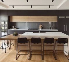 COLOUR COMBINATION Dark cabinetry surround with timber storage above glass splashback. Timber island bench with white benchtop and extended seating. Benchtop would look good in concrete look finish.