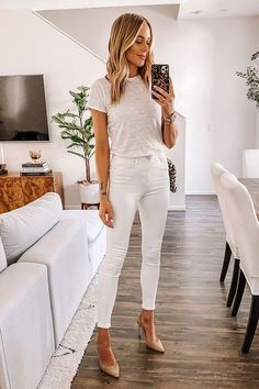 Mujer rubia se toma selfie frente al espejo con outfit blanco