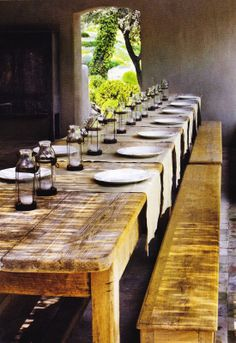 Long rustic natural wood tables and benches, with glass candlelight lanterns, will make an elegant display with plenty of room for food and a clear view of table mates across from guests. Simple and lovely.