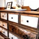 Make over on a thrift store goodwill dresser cowboys up with cowhide and studs. Huge transformation.