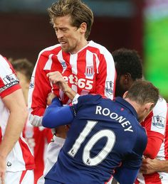 Wayne Rooney clashes with Stoke's Peter Crouch