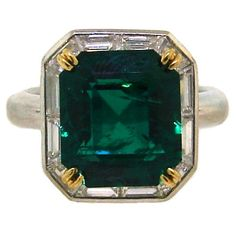 Classic cocktail ring created by Tiffany & Co. in the 1960's. The highlight of the ring, 6.26 carats cut-cornered rectangular step cut emerald, is surrounded by baguette cut diamonds and set in platinum and 18k yellow gold.