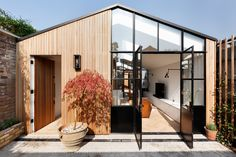 A storage shed was converted into a beautiful, light filled home with glass windows and light wood paneling