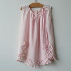 Vintage pink toddler dress finished with ribbons and white cotton inserts at the shoulders, circa 1940.
