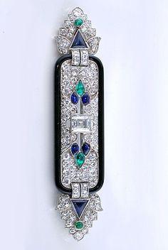 Janesish Broche Art Deco in stile orientale (attorno al 1925) centrata su di un pavè di diamanti incorniciato con onice nero al centro un grande diamante taglio quadrato con ai lati due placche con gocce di zaffiri e smeraldi alle estremità decorazioni con palmette stilizzate di diamanti zaffiri e smeraldi.