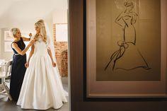 Bridesmaid helping bride get dressed Beautiful lace overlay wedding dress Parklands Quendon Hall Wedding Photography #weddingdress #white #navy #bride #blonde #weddingphotography Image by ARJ Photography
