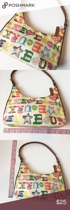 Small Dooney & Bourke Purse Excellent used condition! Authentic Dooney & Bourke Purse Colorful Letters and Star Print. Red interior with 3 compartments (main compartment, side pocket, and side zippered compartment). Leather exterior is in excellent condition, only flaw is several markings (I tried to take pics of them all) and it seems like it may be slightly discolored. It has a more yellow/ brownish tint towards the top, but I can't remember it's original color. But there are no tears or…