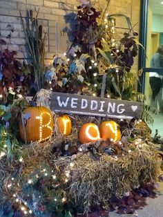 Fall wedding theme. I love the lights on the bale of straw! Not really liking the carved pumpkins. Great for the reception entrance into the building.