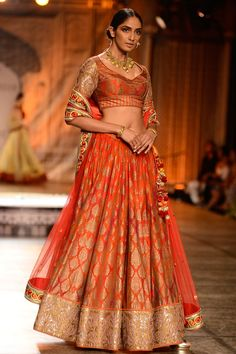 Featuring an orange and red shaded chanderi lehenga with gold sheet printed motifs all over. It has a gold mirror and applique work cotton tissue border. It is paired with a matching block printed blouse with piping highlighting the seams and embroidered sleeves. It comes along with a gold net dupatta with thread work floral border. Fabric: Lehenga: Chanderi, Cotton tissue; Blouse: Chanderi; Dupatta: Net Care Instructions: Dryclean only.
