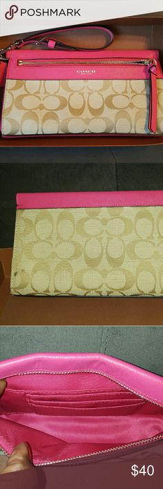 Authentic coach large wristlet Great used condition. Signature material with pink leather trim and strap. Zipper closure. Has pink satin lining with 1 large pocket and 3 card slots. Has a smudge on the back that can be cleaned with a mild soap. Measures 9x4.5x2. Comes from a smoke free home. Coach Bags Clutches & Wristlets