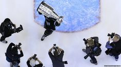 Los Angeles Kings' Jarret Stoll is pursued by photographers as he holds up the Stanley Cup