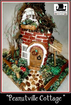 """""""Peanutville Cottage"""" A pleasant gnome house   """"completely- natural"""" built !: a jasmine branch wreath hanging on the door. pinecone roof, bricks, peanut floor, toadstools, straw gazebo with hanging hammock!!!"""