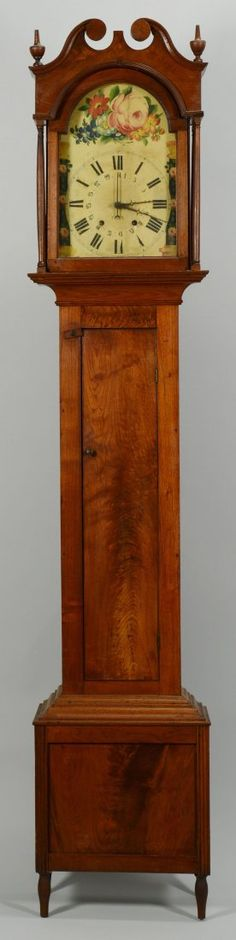 Early 19th century American tall case clock, walnut case with poplar secondary wood, dovetailed bonnet top with broken arch pediment and two classical finials at each front corner, over an arched painted dial with steel hands and two winding holes, floral design in tympanum, behind a glass door flanked by full round turned columns at each corner. Four delicate plain turned and tapered feet. Oral history being from Ohio with works imported from Germany. Case probably Ohio or Kentucky.