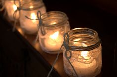 Mason jars used as lanterns. Twine and Lace wrapped around for decoration + a tea light candle