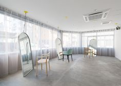 Mirrors hang from cables in Japanese hair salon by Sides Core.