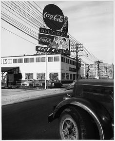 Symbols - Daytime, Coca-Cola Logo - Couple on Billboard on ABC Vending Building, Neon Signs, View over Front Left Fender of a Truck, Telephone Lines, Parking Lot, Commercial Avenue