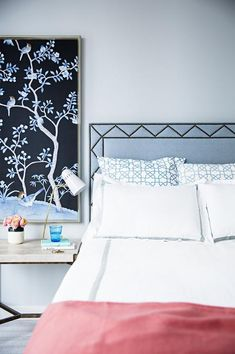 Chic bedroom features a blue headboard with brass nailhead trim on bed dressed in white and gray hotel duvet and shams as well as blue lattice shams placed next to a marble and brass bedside table illuminated by a white and gold task lamp under a frames fabric panel.