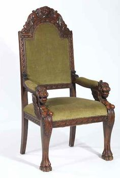 A heavily carved vintage arm chair with substantial griffin arms/front legs, west wind grotesque mask at the top of the heavily carved top rail, upholstered in green velvet with nailhead trim.