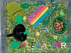 March themed sensory bin:  3 bags of Green Split Peas  Small funnel  2 green spoons   A handful of gold stones   A few green felt flowers  Stripes of craft foam in rainbow colors to create a rainbow  2 paper leprechauns