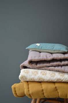 Play with colour and print using Camomile london hand quilted blankets.
