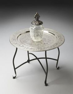 Inspired by a traditional Moroccan tea table, this tray table is embellished with vines and bunches of grapes on its aluminum serving tray. The lightweight alum