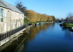 An East Anglian riverfront in England.   We stand looking downstream on this bright, cloudless day.   The old building on our left was once a busy mill, and the remains of an old wince can still be seen. Nowadays, however, this commercial use is no longer needed, and it has been converted to a terrace of charming riverside properties.