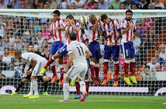 Gareth Bale of Real Madrid shoots a free kick over the Atletico de Madrid wall of defenders during the La Liga match between Real Madrid and Atletico de Madrid at Estadio Santiago Bernabeu on September 13, 2014 in Madrid, Spain.