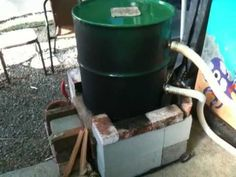 now this homemade rocket stove heats a pool. black hose in the barrel. how creative!