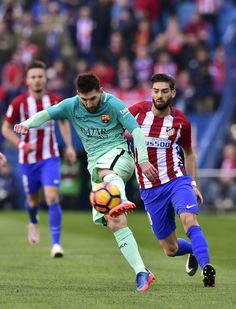 Barcelona's Argentinian forward Lionel Messi (L) vies with Atletico Madrid's Belgian forward Yannick Ferreira Carrasco during the Spanish league football match Club Atletico de Madrid vs FC Barcelona at the Vicente Calderon stadium in Madrid on February 26, 2017. / AFP / GERARD JULIEN