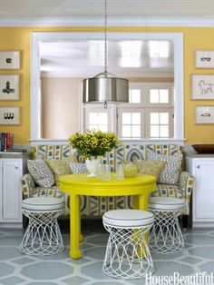 Bright yellow walls—Benjamin Moore's Inner Glow—and an even brighter citron table from HB Home brought to life this white-and-gray kitchen by designer Lindsey Coral Harper. Harper turned wire side tables from ABC Carpet & Home into stools. Dark brown floors were transformed with a large geometric pattern, painted by Jay C. Lohmann. Pendant light from Robert Abbey. Hugo Guinness prints from John Derian.