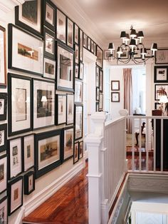 Proper lighting and striking artwork add style to a small space.  ~Tigerwood flooring in the home's upstairs hall sets off the sepia tones in some of the many works on display. A curvacious black and white chandelier harmonizes with the frames.