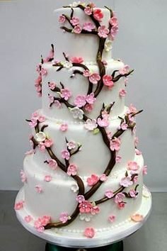 A four tier round white cherry blossom wedding cake is beautifully decorated with pink sugar flowers made to look like real cherry blossoms.