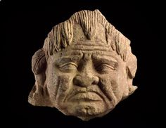 Head of a grimacing yaksha, or nature spirit , Mathura,2nd - 3rd century AD (AD 101 - 300)	 Kushan Period (AD 50 - 600),mottled pink sandstone. Yaksha- in the mythology of India, a class of generally benevolent nature spirits who are the custodians of treasures that are hidden in the earth and in the roots of trees.