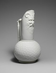 Cool pitcher! Looks like the face of a Roman Satyr (I think?)