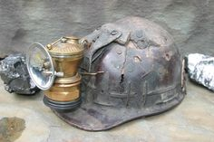 This is an example of what a carbide light looks like when it is attached to the Skullgard Helmet that was introduced into the industry after 3 mining explosions that killed a large amount of miners. (https://s-media-cache-ak0.pinimg.com/736x/b6/d2/ce/b6d2ce5c2968ff974fd81a48da00f673.jpg)