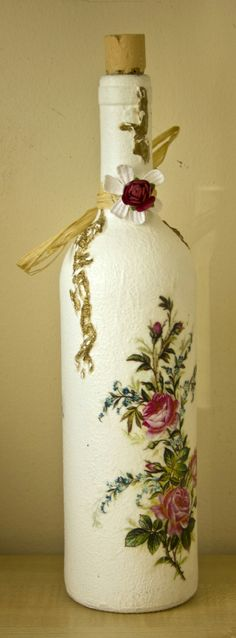 More decoupage on a wine bottle this time, using rice paper, texture paste and raffia. Texture paste followed by undercoat and two coats of white acrylic. Painted texture paste with gold acrylic and decoupaged rice paper images with sandings between coats of varnish Finished with final coat of varnish.