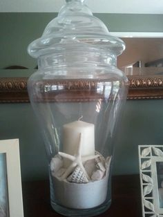 Apothecary jar filled with sand, shells, and a candle.