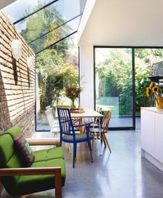 A bright glass-roofed extension has replaced a gloomy side alley the architects designed and made the tabletop with metalworkers the blue chair is by Yinka Ilori and the Danish sofa from # Glass Roof Extension, House Extension Design, House Design, Side Extension, Cottage Extension, Extension Ideas, Kitchen Extension Windows, Kitchen Extension Side Return, Conservatory Extension