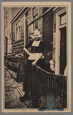 VAN EIGEN LAND 1940-1950 Een Volendamse vrouw in dracht voor een houten woning in het Doolhof te Volendam. Op de voorgrond een fraai houten hekje. #NoordHolland #Volendam