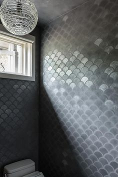 Modern gray bathroom features walls clad in gray metallic fishscale tiles lined with a toilet situated under a Juliska Amalia Globe Pendant.