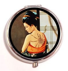 Japanese Geisha Pill Box is offered here. She has a large, very strange, unique spider tattoo being applied to her back. This vintage 1890s era illustration is odd and unique! You totally want this! This vintage tattooed Japanese geisha woman pillbox will amaze and delight you every time you use it!  Uses: Pill Box, Pill Case, Vitamin Holder, Medicine Organizer, or Trinket Box Other Uses: Accessory for guitar picks, coins, buttons, & other small items Color: Stainless Steel Condition: Bra...