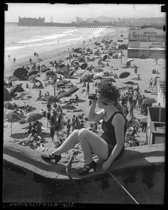 Girl with spy glass looking out from the pier with crowded beach in background, Los Angeles, California. Santa Monica pier circa 1920.