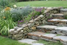 I great way to transition from one level of the yard to the next with these natural stone steps and stone garden wall.