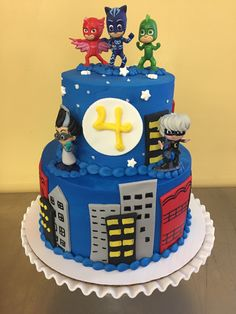 Two tiered cake covered in buttercream with fondant city scape and PJ Mask figurines, purchased separately.
