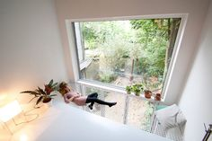 Dutch architects Gwendolyn Huisman and Marijn Boterman designed this skinny house in Rotterdam for themselves, incorporating hidden windows into the black brick walls and adding a large indoor hammock.