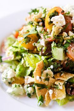 Syrian Fattoush Salad from Insalata's in San Anselmo.  Hearts of romaine, cherry tomatoes, cucumber, red onion, feta, cilantro, mint, kalamata olives in a lemon-garlic-cumin dressing.  Recipe here: http://www.insalatas.com/recipes/recipes05.html