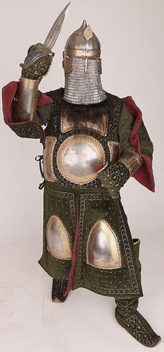 Indo-Persian armor / Indian chilta hazar masha (coat of a thousand nails), armored clothing made from layers of fabric faced with velvet and studded with numerous small brass nails, which were often gilded, and Ottoman style chichak helmet which was originally worn by cavalry of the Ottoman Empire, dastana (arm guards) and katar (push dagger). Fabric armor was very popular in India because metal became very hot under the Indian sun. This example has additional armor plates in the chest, arm…