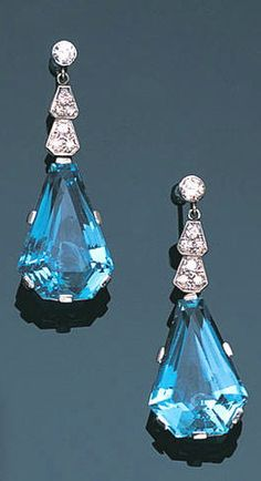 A pair of aquamarine and diamond pendent earrings, circa 1945 Each brilliant-cut diamond surmount suspending geometric motifs of brilliant and single-cut diamonds, terminating in a calf's-head-cut aquamarine, length 3.7cm.