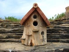 A very unique birdhouse made from cedar log. The construction process for this birdhouse involves cutting logs to length, stripping bark to reveal the natural beauty of the grains in the log, hollowing out the log, then adding a variety of wire and stone accents. Pictured is a hanging birdhouse where the bottom can be easily removed for seasonal cleaning. #ad:
